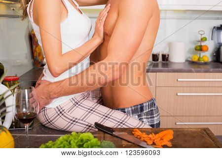 Couple having foreplay in the kitchen while cooking
