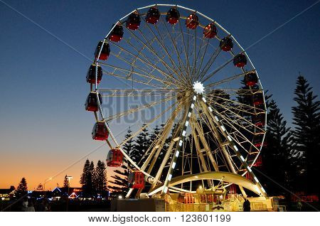 FREMANTLE,WA,AUSTRALIA-SEPTEMBER 30,2015: Ferris Wheel amusement ride lit up at twilight with red gondola's  and people in Fremantle, Western Australia.