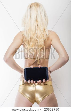 Longhair blonde captured from behind holding black tablet pc in her hands showing buttocks in golden hot pants