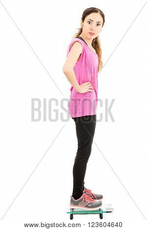 Woman measuring her weight and looking shocked at her weight. Isolated on white background.