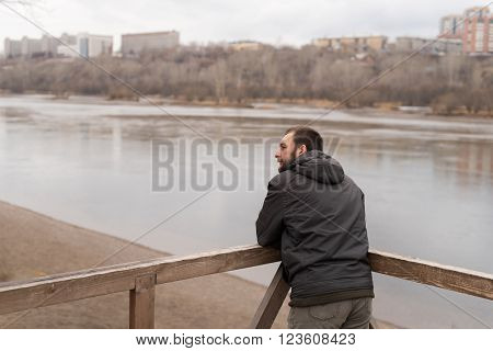 Bored man leaning his  elbows on railing and looking at the river