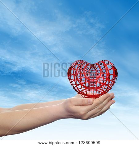 Concept or conceptual 3D red abstract heart sign or symbol held in hands by woman or child over nice blue cloud sky background