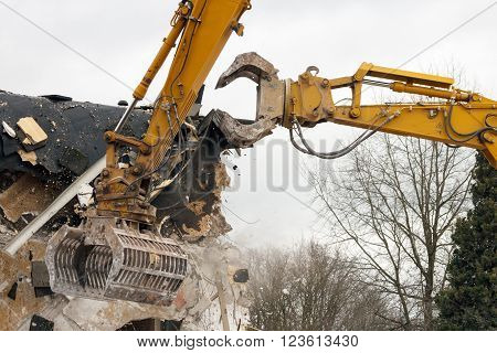 Two yellow demolition cranes dismantling a building
