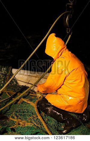 Trawl master repairs fishing trawl. Night time.