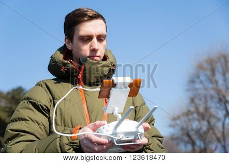 Young man holding a controller and controls the drone