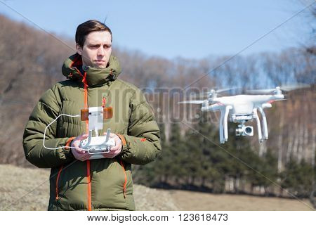 Young man controls the drone in open terrain