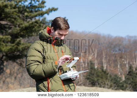 Man controls the flying drones in the spring