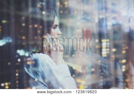 Photo woman wearing white shirt, talking smartphone and holding business plans in hands. Open space loft office. Panoramic windows, night city background. Horizontal mockup