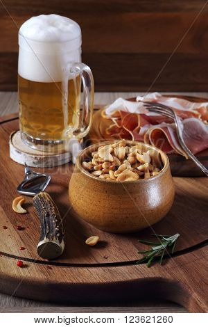Unfiltered beer, nuts and  cold cuts on wooden board