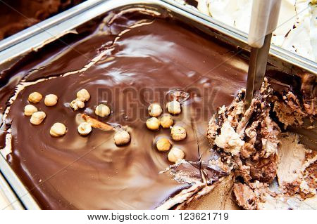 Tub of delicious Italian chocolate nut ice cream topped with whole roasted hazelnuts in a stainless steel tub with a scoop in retail store