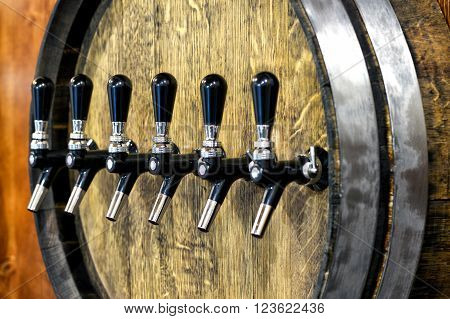 Large oak wine barrel with a row of spigots for serving draught wine to customers in a winery, tavern or pub, close up view