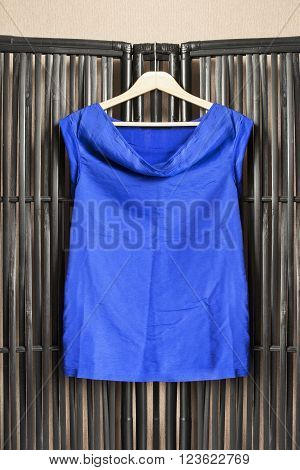 Blue silk shirt on clothes rack hanging on black bamboo screen