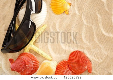 Sunglasses seastar and seashells in sand closeup