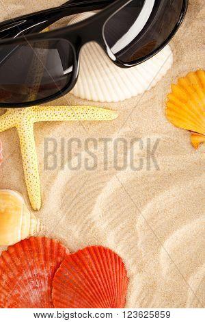 Sunglasses, Seastar And Seashells In Sand