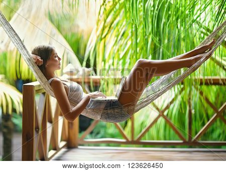 Young beautiful woman lying in a hammock with laptop in a tropical resort
