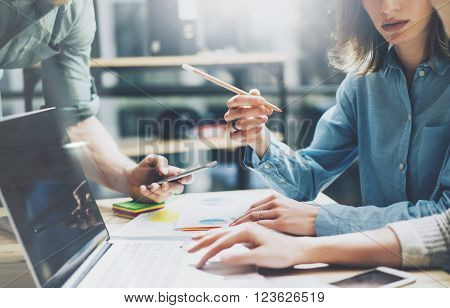 Coworking process. Photo young business crew working with new startup project. Notebook on wood table.  Woman showing screen laptop, man holding smartphone. Blurred background, film effect.