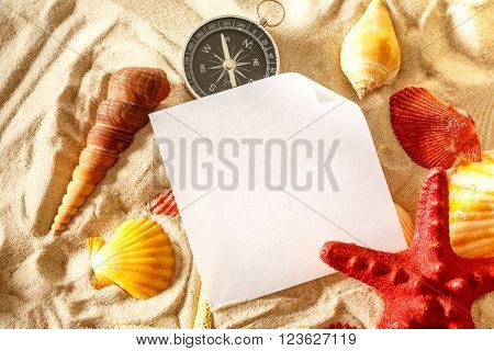 Seashells, Compass And Paper On Sand