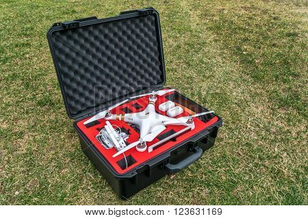 Fort Collins, CO, USA - March 12 2016:  DJI Phantom 3 quadcopter drone with a set of propellers, radio controller, iPad tablet and spare batteries in a waterproof case on grass