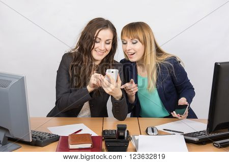 Two Office Workers Enthusiastically Discussing Something On A Mobile Phone At His Desk