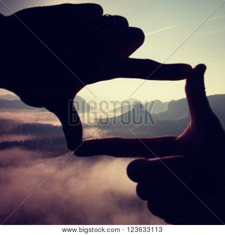 Fingers Frame. Close Up Of Hands Making Frame Gesture. Blue Misty Valley Bellow Rocky Peak. Sunny Sp