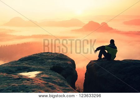 Young man in sportswear is sitting on cliff's edge and looking to misty valley bellow