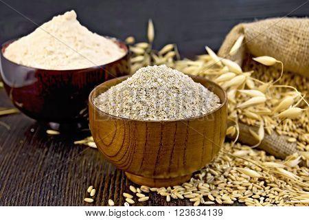 Bran flakes oat and oat flour in two wooden bowl, a bag of grain oats, oat ears against the dark wooden board
