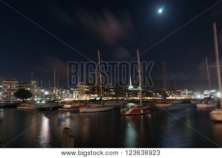 Long exposure city lights across bay boats in foreground blurred while gently rocking and city buildings light reflected on water Wellington Harbor New Zealand