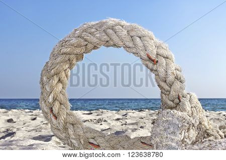 Old plaited artificial thick rope twisted into a ring lying on the seashore