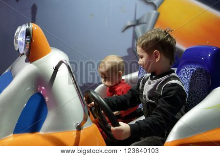 Two boys playing arcade game machine at an amusement park