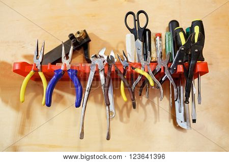 Workshop tools pliers clamps on the stand on the wall, a pair of scissors, bender, screwdrivers, power indicator, an adjustable wrench.