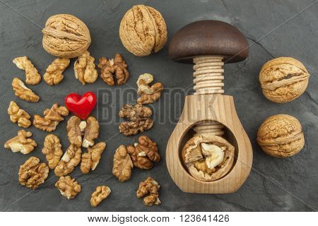 Walnut kernels and whole walnuts on slate.  Walnuts and wooden nutcracker. We like walnuts. Advertising on walnuts.