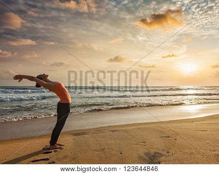 Young sporty fit woman doing yoga Sun salutation Surya Namaskar pose Hasta Uttanasana on tropical beach on sunset