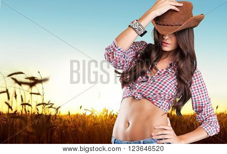Portrait of a beautiful woman wearing  cowboy's hat with wheat field on background