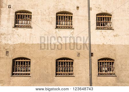 Jail wall with windows with bars on a wall