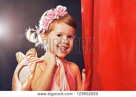 little child girl ballerina ballet dancer on the stage in red side scenes