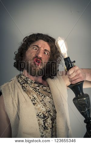 Silly realistic caveman dumbfounded by confusing lightbulb