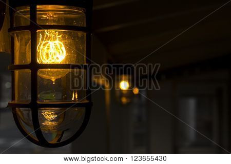 Decorative antique style filament light bulb outside at night