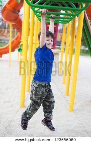 Little boy hanging on jungle gym in park