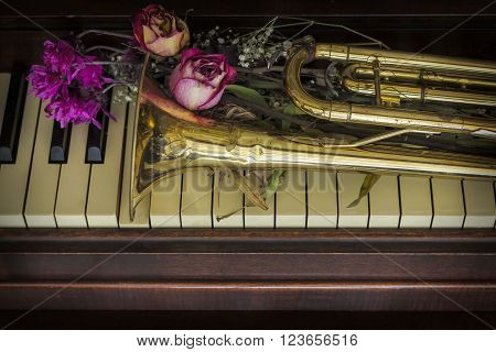 Old and worn Jazz trumpet and piano with dried flowers