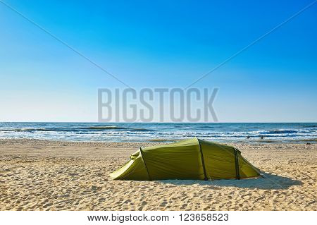 camping with a tent at a lonesome beach with a turquoise sea and blue sky in the background