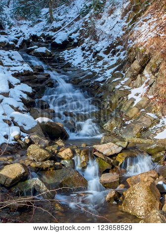 frozen waterfal with transparent fresh water in the mountain