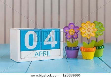 April 4th. Image of april 4 wooden color calendar on white background with flowers. Spring day, empty space for text. Webmaster Day.