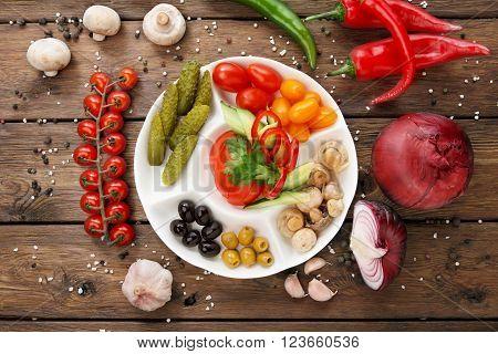 Restaurant appetizer food. Restaurant food assortment plate. Pickled vegetables, tomato, cucumber, pepper, olives platter in restaurant. Catering, served table. Pickled vegetables food plate. Top view