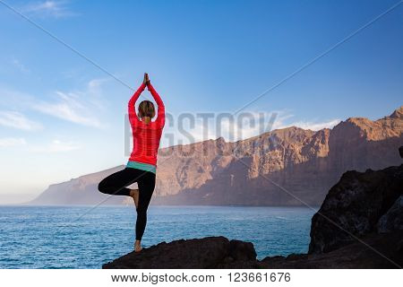 Woman meditating in yoga vrksasana tree pose silhouette at the ocean beach and rock mountains. Motivation and inspirational fit and exercising. Healthy lifestyle outdoors in nature fitness concept.