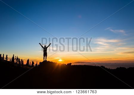 Man hiker silhouette with arms outstretched in mountains. Male runner or climber looking at sunset view. Business concept and hands up and enjoy inspirational landscape rocky trail footpath on Tenerife Canary Islands
