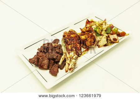 Surf and turf, fried lobster and juicy stake with a garnish from fried vegetables