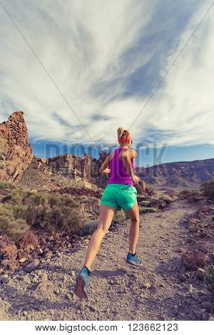 Woman trail running in mountains on dirt path. Beauty female runner jogging and training with backpack outdoors in nature cross country running on rocky trail footpath on Tenerife with Teide mountain in background Canary Islands.