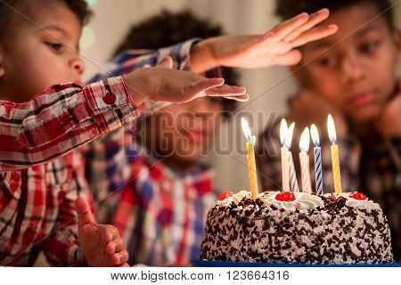 Kid holds hand over candle. Boy's hand over cake's candle. Friends will be impressed. I'll show you a trick. ** Note: Shallow depth of field