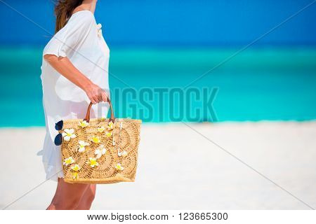 Beach accessories - adorable bag with frangipani flowers and sunglasses on white beach