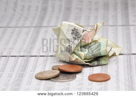 Crumpled Thai banknote and small change on stock quotes sheet.